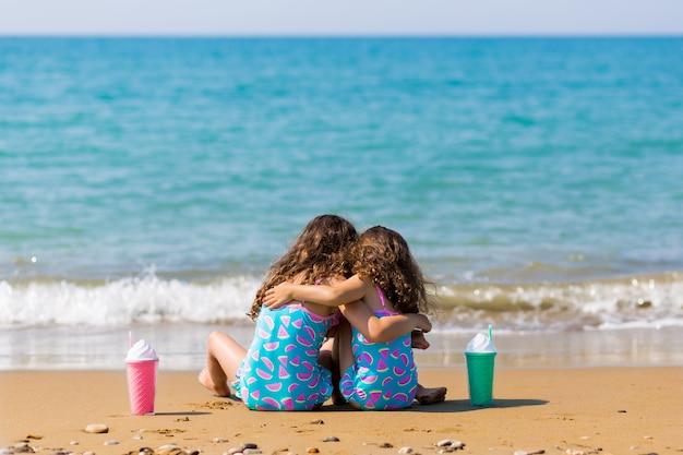 少女たちはカクテルとともに砂の上に座って寄り添います。家族での休暇の概念。幸せな姉妹