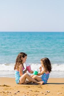 小さな女の子が座ってお互いの反対側に座るし、色の美しいカクテルグラスの家族休暇の概念から飲む