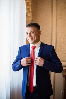 赤いネクタイと若い幸せな男は窓の近くに立っている青いスーツを着ています。