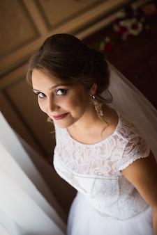 窓の近くに立って、笑顔の美しい花嫁