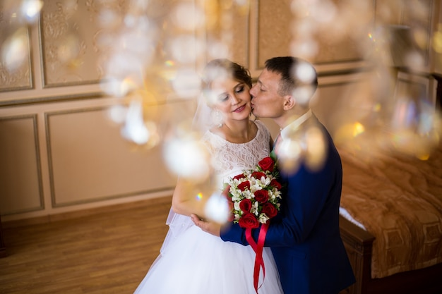 Жених и невеста целуются в гостиничном номере, держат свадебный букет