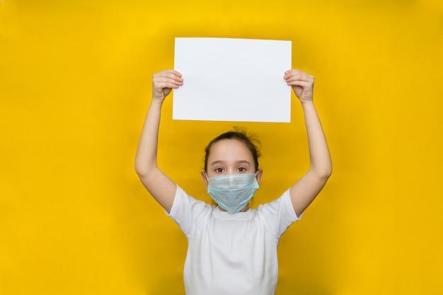 防護マスクの少女は、彼女の上に紙の空白のシートを保持しています。コロナウイルスに対する保護