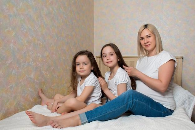 幸せな妊娠中の母親は、部屋のベッドに座っている娘の髪をとかしています。幸せな愛情のある家族