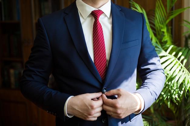 ネクタイを結ぶ青いスーツのビジネスマン。