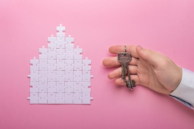 Белая головоломка. дом в форме головоломки. понятие аренды, ипотеки. рука держит ключи. вид сверху