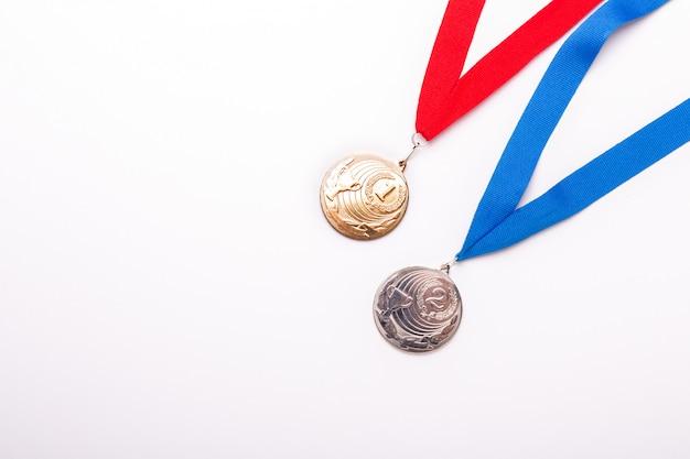Золотые и серебряные медали с лентой на белом фоне.