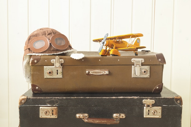 Шлем пилота и игрушечный самолет из желтого металла два старых ретро чемодана белый деревянный фон винтажная тонировка