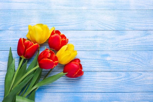 木製のテーブルに新鮮な色とりどりのチューリップの花の花束