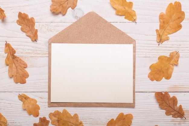 秋の紅葉と白い木製の背景上の封筒。フラットレイアウト、上面図、コピースペース。