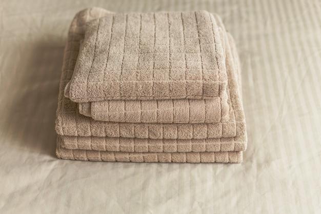 寝室のインテリアのベッドの上のベージュのホテルタオルのスタック。ビンテージ調色