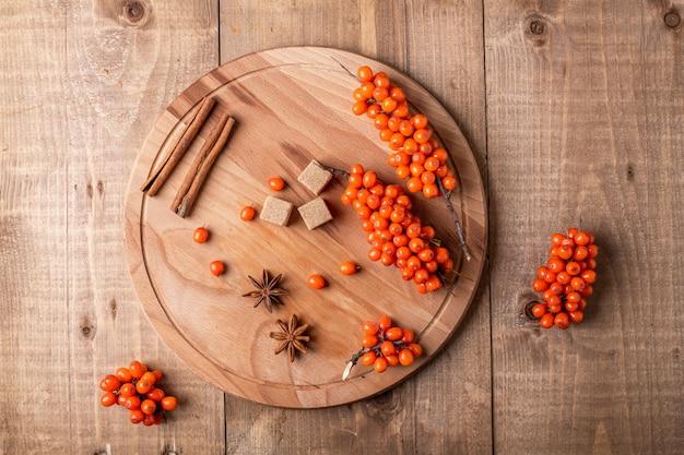 海クロウメモドキの果実と木製の背景にスパイス。素朴なスタイル