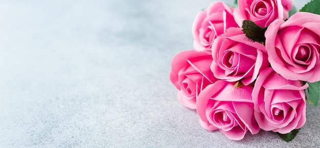 石の背景にピンクのバラの花の花束