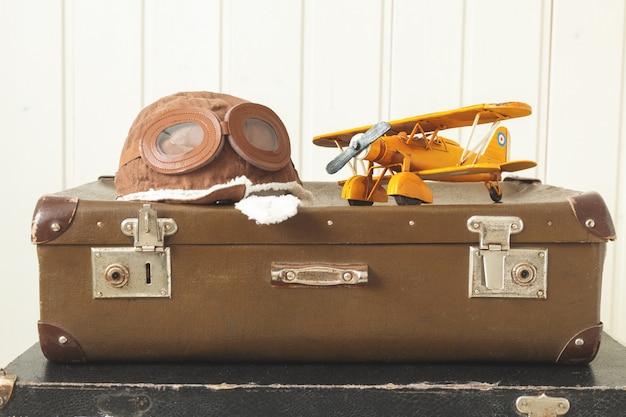 Шлем пилота и игрушечный самолет из желтого металла. два старых чемодана в стиле ретро. белое дерево.