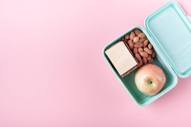 Ланч-бокс с яблоком, бутербродом и миндалем на розовом