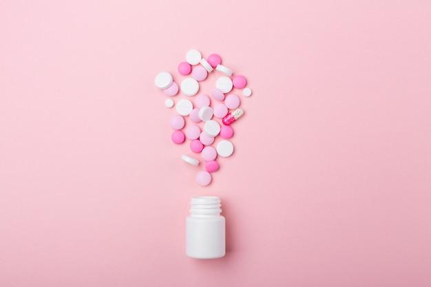 ピンクの背景にピンクと白の錠剤ペットボトルヒープ各種詰め合わせ様々な薬の錠剤や丸薬。健康管理。