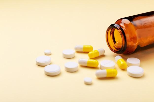 黄色のガラス瓶から多色錠剤や丸薬カプセル