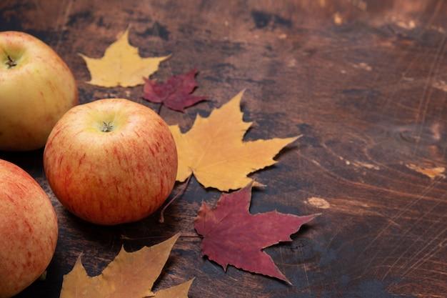 リンゴと黄色の赤いカエデの葉の古いグランジ木製の葉