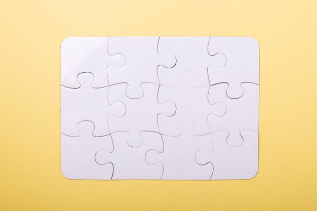 Кусочки головоломки на желтом