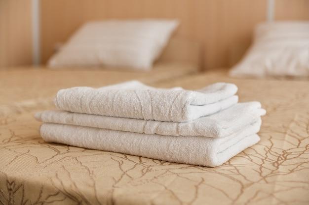 Стог белого полотенца гостиницы на кровати в интерьере спальни.