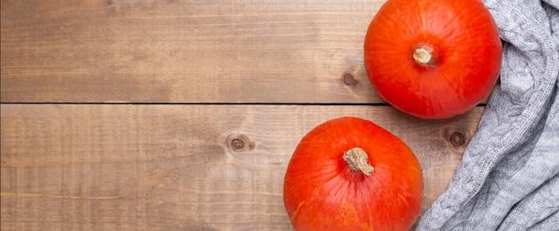 オレンジ色のカボチャ、木製の居心地の良いセーター。水平バナー