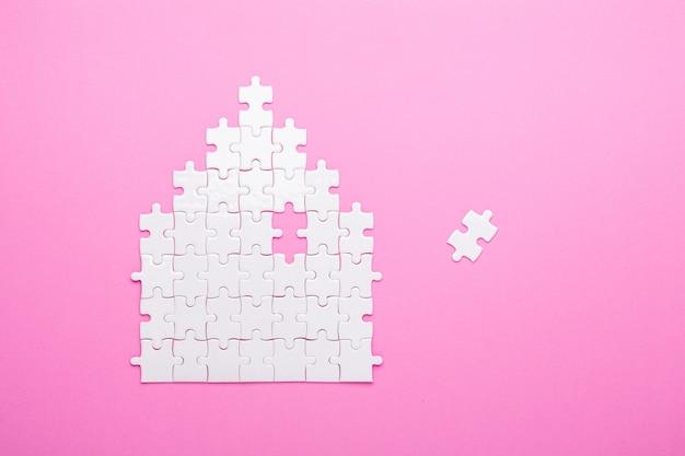 白いパズル。家の形のパズル。家賃、住宅ローンの概念。上面図