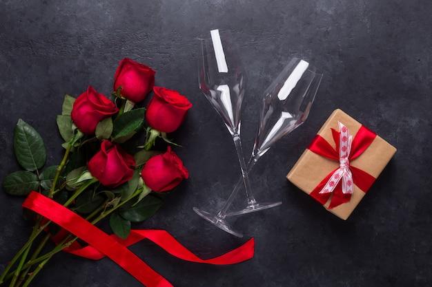 赤いバラの花束、ギフト用の箱、黒い石の上のシャンパングラス。バレンタイン・デー