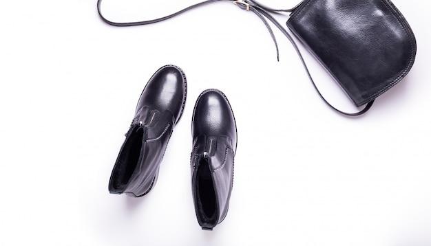 女性のアクセサリー。黒のスタイリッシュなブーツ、黒の高級レザーバッグ。上面図。フラット横たわっていた。