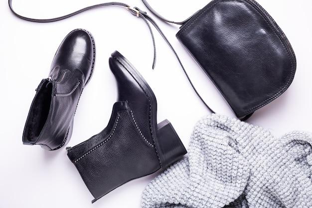 女性のアクセサリー。黒のスタイリッシュなブーツ、黒の高級レザーバッグ、グレーのスカーフ。上面図。フラット横たわっていた。