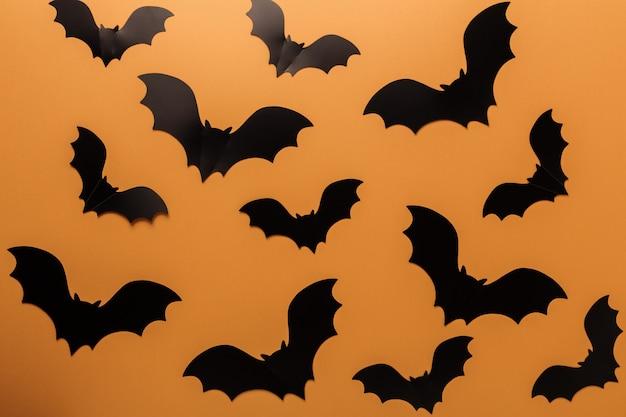 オレンジ色の背景にハロウィーン黒コウモリ