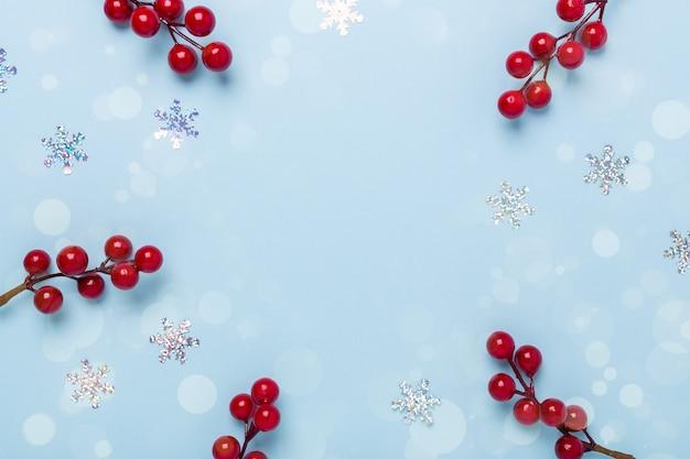 Рождественская композиция рамка со снежинками и и холли ягод на пастельном синем фоне