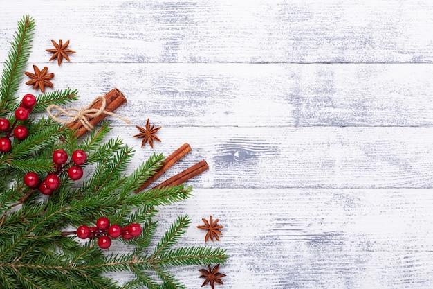 モミの木とシナモンのクリスマス背景は、木製のテーブルにスティックします。水平バナー