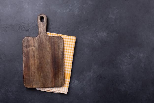 Разделочная доска и льняная салфетка на темном фоне стола
