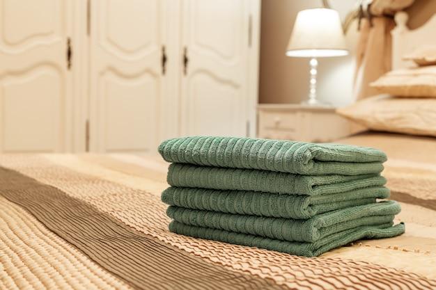 Стог зеленого гостиничного полотенца на кровати в интерьере спальни