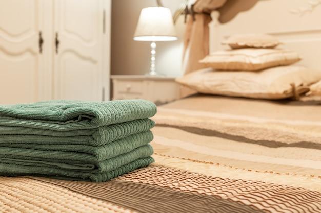 寝室のインテリアのベッドの上の緑のホテルタオルのスタック