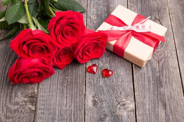 Красные розы цветы и подарочная коробка на сером деревянном столе
