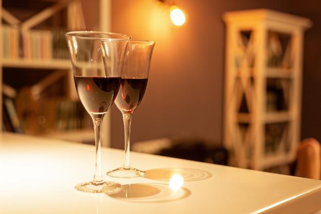 Два бокала красного вина в уютном интерьере