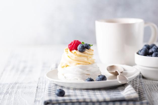 ホイップクリームと新鮮な果実のおいしいパブロワケーキ。白い一杯のコーヒー。