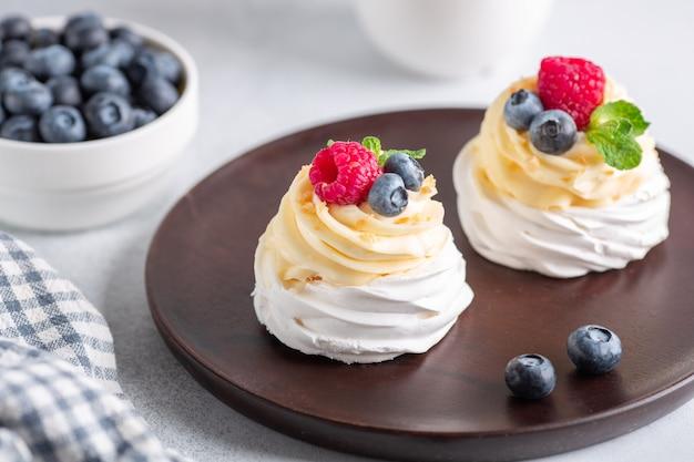 Вкусный торт павлова с взбитыми сливками и свежими ягодами на деревянной тарелке.