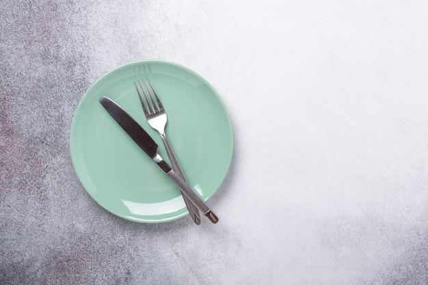 Мятная тарелка и столовые приборы. копировать пространство вид сверху