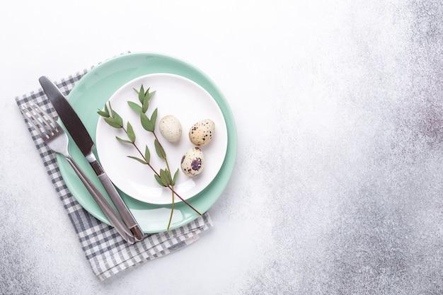 Пустые мяты и белые тарелки, льняная салфетка, листья эвкалипта и яйца. сервировка пасхального стола