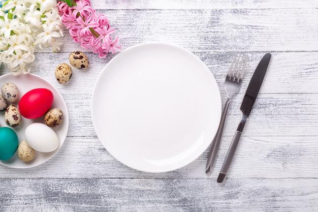 春のテーブルセッティング。緑のミントプレート、イースターエッグ、ヒヤシンス、木製の背景に銀のカトラリー。コピースペース。上面図