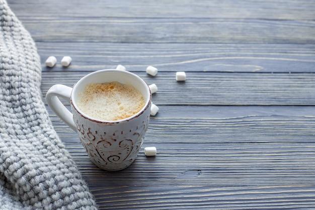 Чашка кофе с зефиром на деревянном фоне