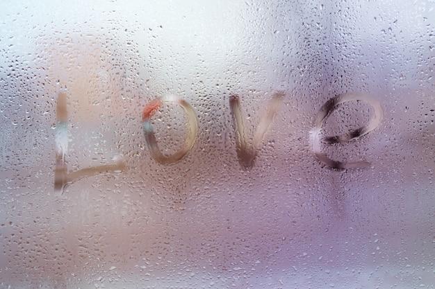 雨の滴のあるウィンドウ上の愛という言葉