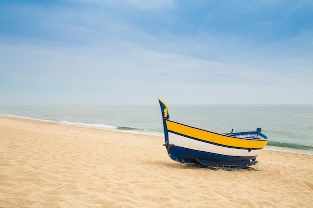 Деревянная рыбацкая лодка на песчаном пляже