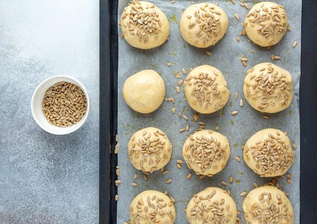 Сырые шарики из теста, посыпанные семенами на сковороде