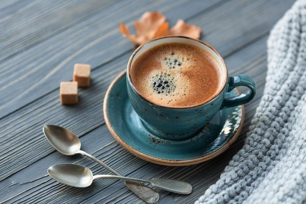 Синяя чашка с кофе с вязаным свитером