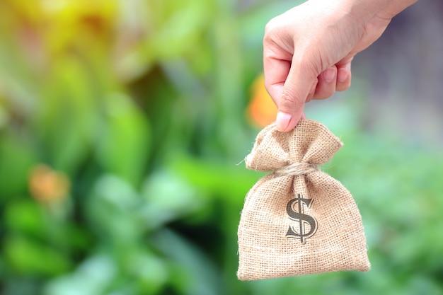 アイデアを取引するためのお金の袋を持つ女性の手。または金銭的投資。