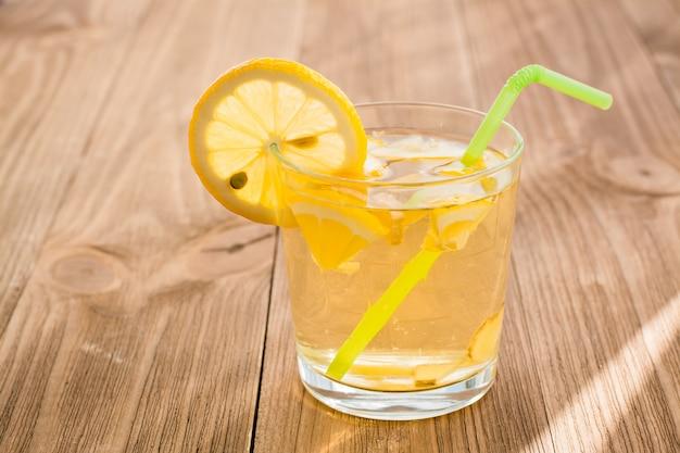 木製のテーブルにレモンジンジャーの冷たい飲み物とグラス