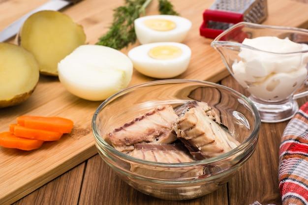 Консервированные сардины в миске и ингредиенты для приготовления салата мимоза