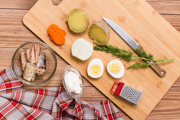 Ингредиенты для приготовления рыбного салата мимоза на столе, вид сверху